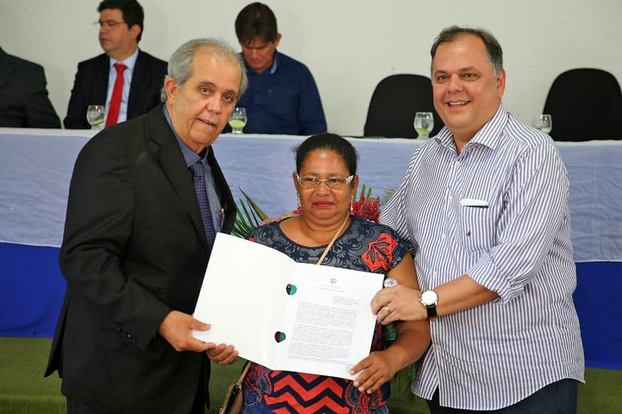 Maria Cristina recebeu o título de propriedade das mãos do desembargador Celyrio Adamastor (à esquerda) e do prefeito Davi Brandão.
