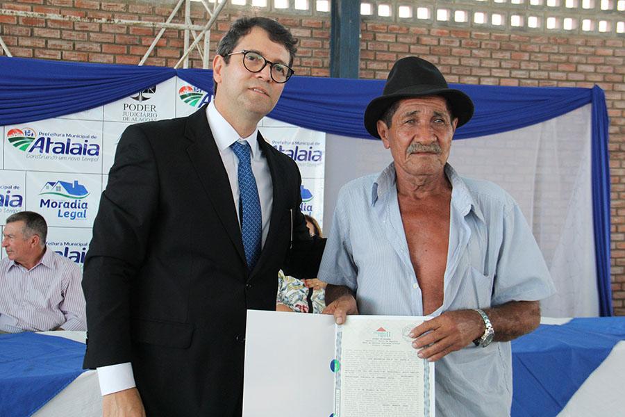 Juiz Henrique Teixeira entrega escritura para morador de Atalaia.