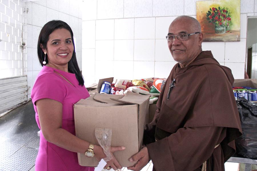 Servidora Érika Lima entrega doação para o Frei José.
