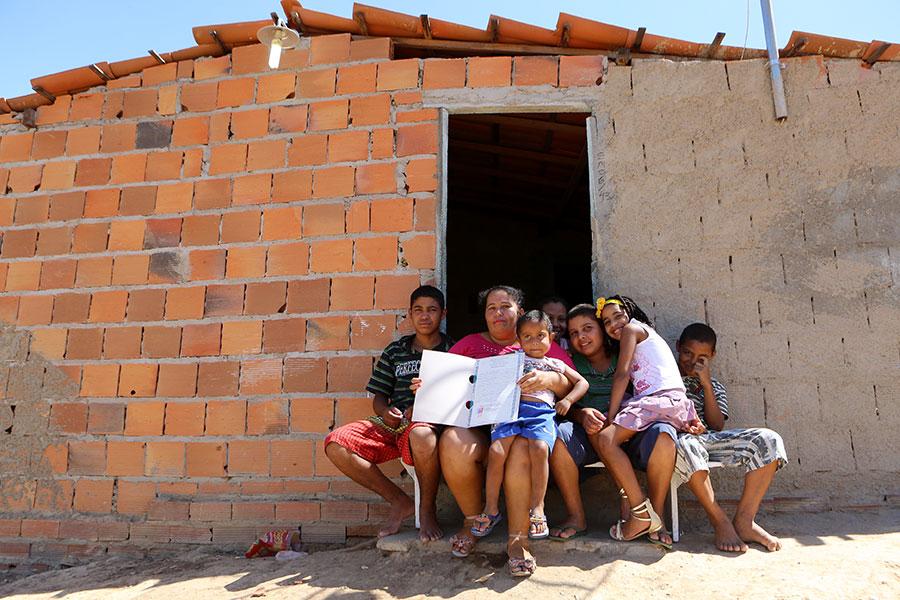 Família de dona Lenira Barbosa exibe título de propriedade, em frente à sua casa em Mata Grande, em 2015.
