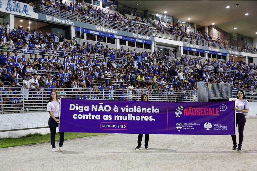 As juízas Marcella Garcia e Carolina Valões, junto com a servidora Ana Paula, exibiram faixa da campanha Agosto Lilás.